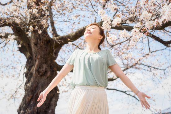 女性が桜が咲く木の下で深呼吸している写真